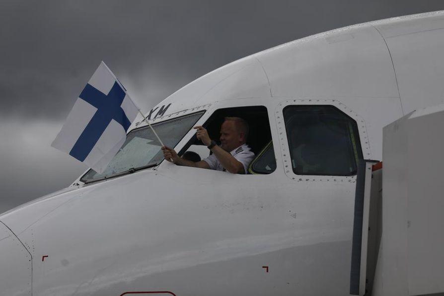 Kultajoukkueen kapteeni heilutti Suomen lippua ikkunasta.