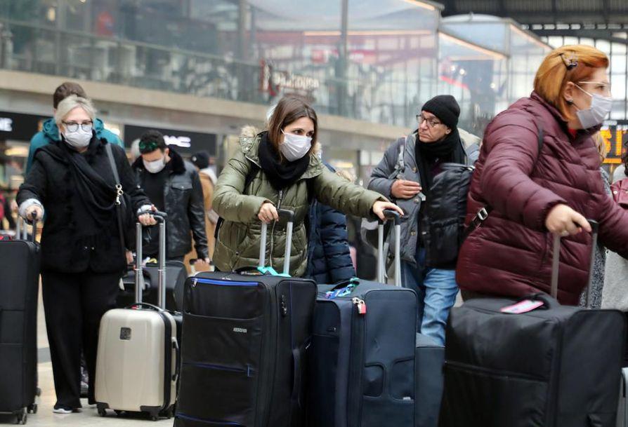 Matkustajat pukeutuivat hengityssuojiin Milanon rautatieasemalla. Koronavirus levisi äkisti Pohjois-Italiassa viikonloppuna. Perjantaina tartuntoja oli havaittu kolme, tiistai-iltana jo yli 280. Myös suomalaisnainen sai koronaviruksen Milanossa.