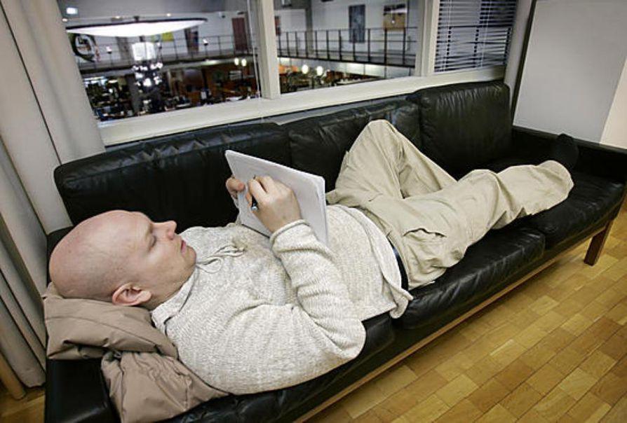 """Etätyöntekijä Toni Pitkälä voi ottaa kirjainten kanssa näpräämisen rennosti, vaikka sohvalla loikoillen. """"Tarkka työ vaatii välillä rentoutumista."""""""