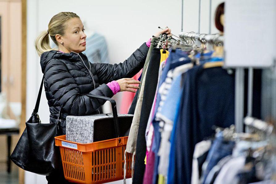 Oulun kierrätyskeskuksen asiakas Anu Koutuaniemi katseli vaatteita uusien tilojen avajaisissa samalla, kun toi itse tavaroita kierrätettäväksi.