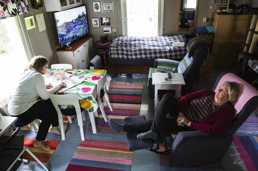 Ebla Katainen istuu tuvassa lempipaikallaan nojatuolissa. Sisko Sissu Soininen lukee, mitä Savon Sanomat kirjoittaa Siilinjärven huippu-uutisesta.