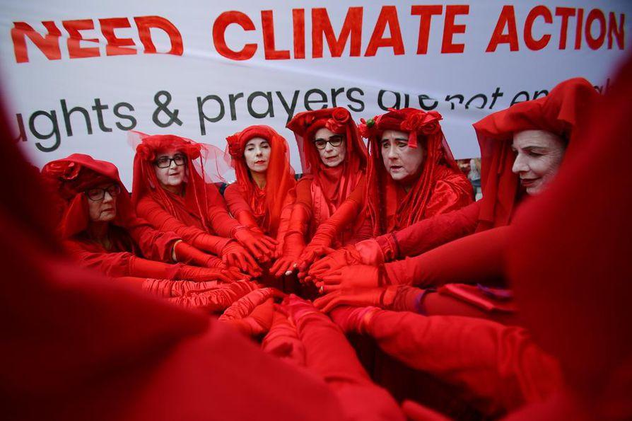 """""""Punaiset kapinalliset"""" osoittivat mieltään ilmastonmuutoksen vastaisten toimien puolesta liberaalipuolueen toimiston ulkopuolella Australian Sydneyssä perjantaina."""