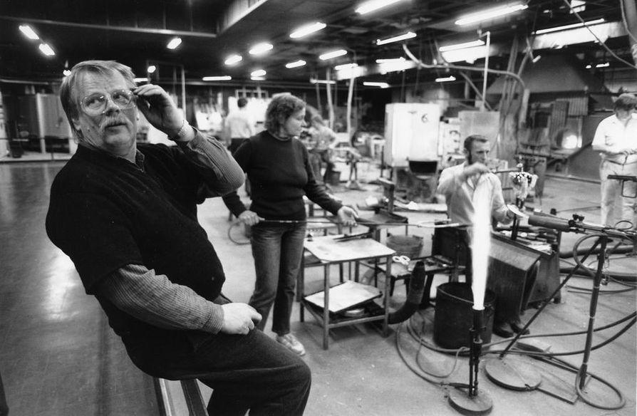 Professori Oiva Toikka (1931–2019) oli Nuutajärven lasitehtaalla suunnittelijana 1960-luvulta lähtien. Hän suunnitteli töitään lasihytissä yhdessä puhaltajien kanssa, ei työpöydän ääressä. Kuva on vuodelta 1987.