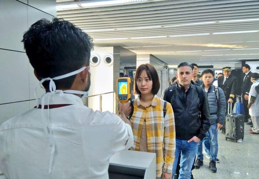 Intian viranomaisten kuvasta näkyy, miten Intiaan Kiinasta, Hongkong mukaan lukien, saapuvia matkailijoita tarkastetaan Kolkatan lentokentällä viruksen varalta.