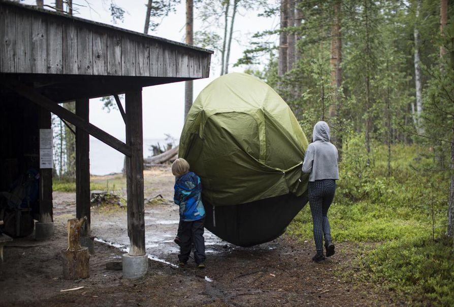 8-vuotias Oskari ja 12-vuotias Alisa auttavat kantamaan telttaa. Sadepäivä ei retkeiijöitä haittaa.