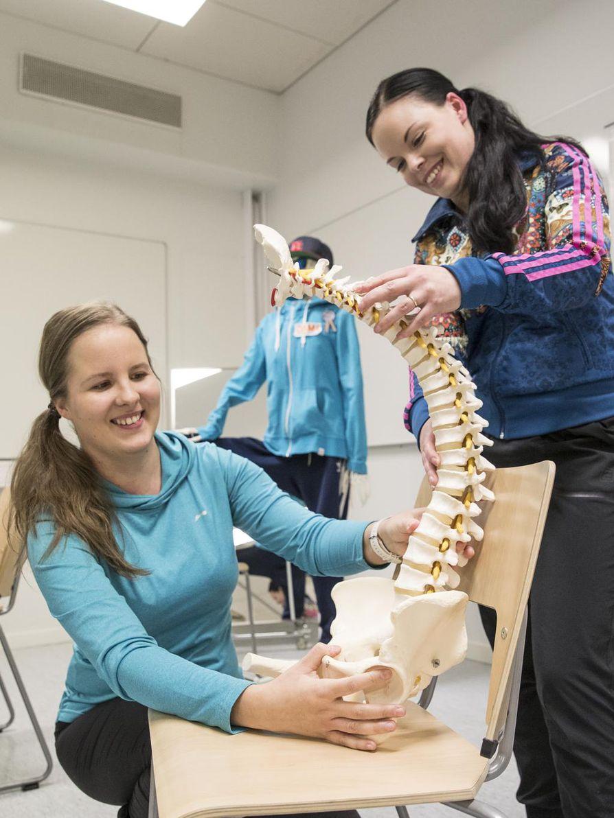 Fysioterapeuttiopiskelijat Elina Lääperi (vas.) ja Niina Backman toivovat muidenkin koulujen hyödyntävän opasta. Taustalla Kalle-luuranko, oppaan kertoja.