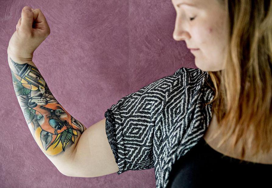 Lähihoitaja Henna Perkiön käsivarressa on värikäs tatuointi.