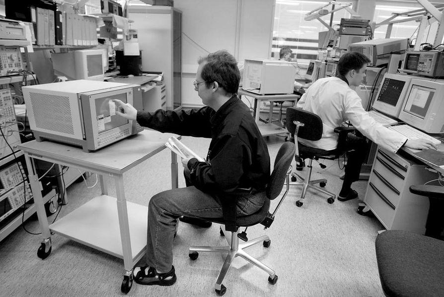 Elektrobit on toiminut useassa osoitteessa. Vuonna 2003 tuotantoteknikko Kimmo Hietala (vas.) testasi radiokanavasimulaattoria Teknologiakylässä Linnanmaalla. Oikealla testaaja Antti Tyvelä.