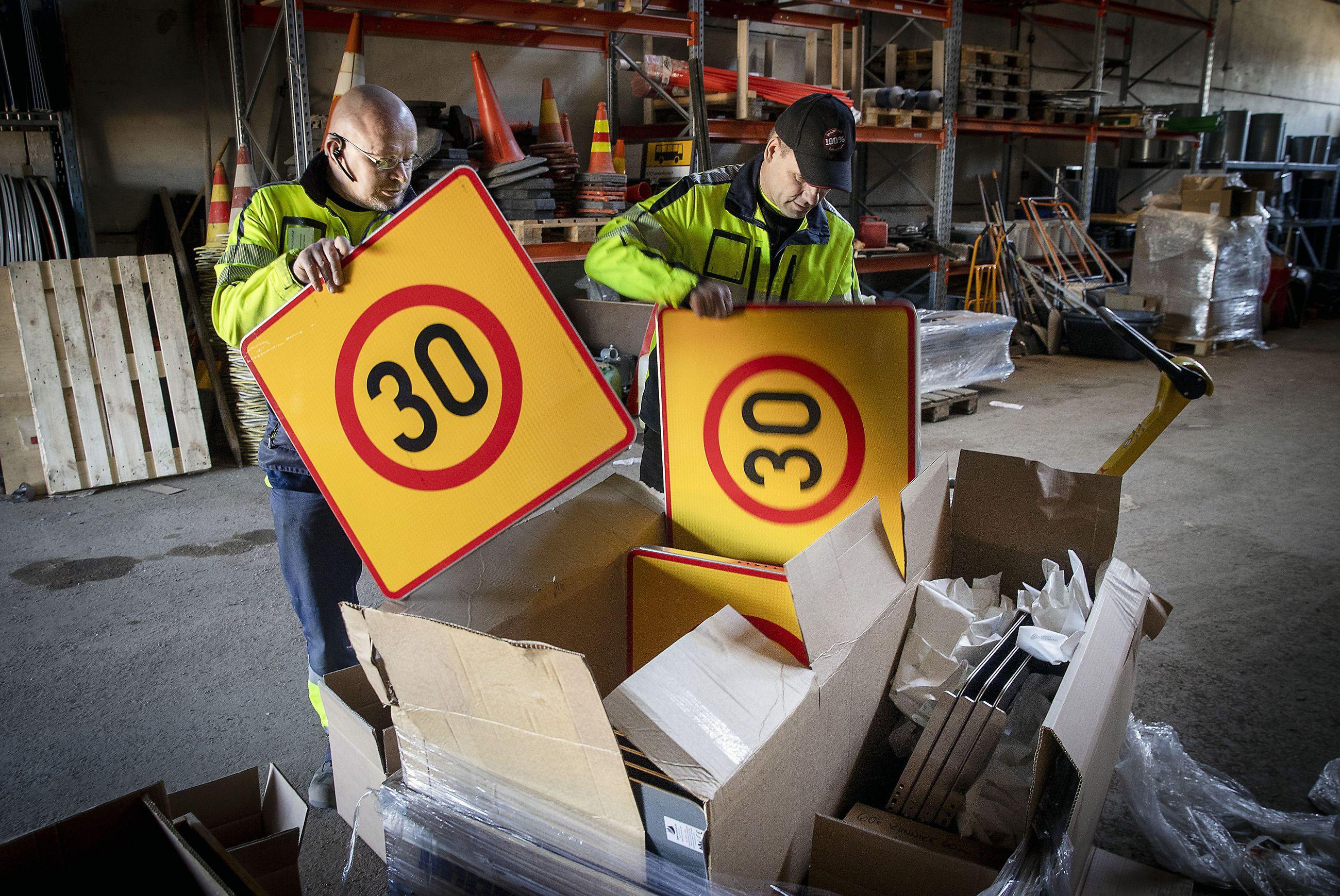 Alueellisia nopeusrajoituksia on alennettu Oulussa viime aikoina 30 kilometriin tunnissa. Kunnossapitotyöntekijät Rauno Oikarinen (vas) ja Seppo Komminaho purkamassa kylttejä arkistokuvassa.