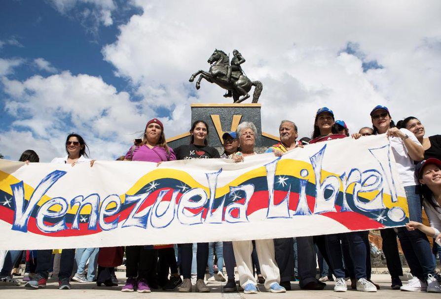 Tuhannet ihmiset kerääntyivät Venezuelassa kaduille keskiviikkona. Kyltissä vaadittiin Venezuelan vapauttamista.