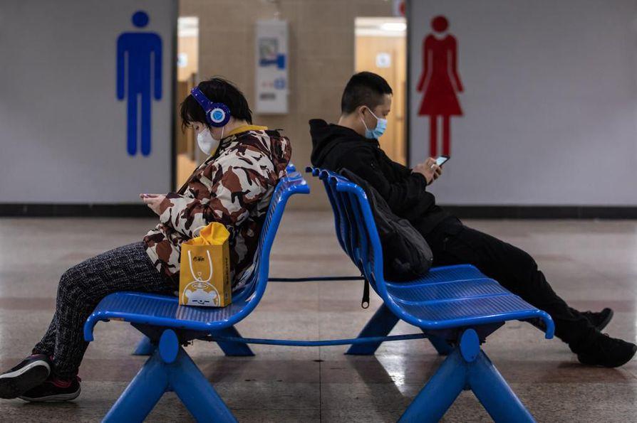 Koronaviruksen leviämisen vuoksi ihmiset käyttävät maskeja useilla lentoasemilla. Kuva Shanghain lentoasemalta.