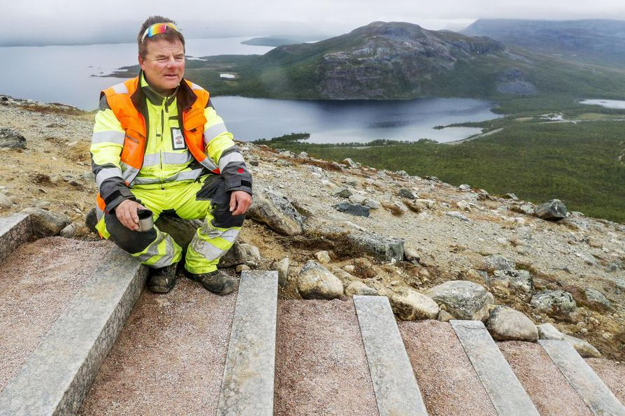 Erkki Törmänen rakentaa portaiden yläpäähän ylimääräisistä kivipalkeista penkkejä.