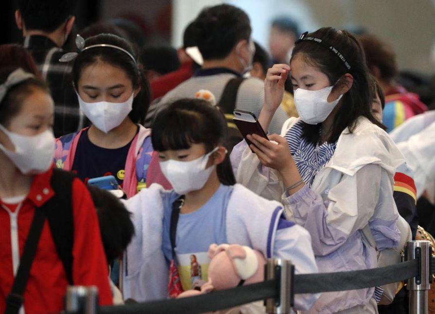 Lapset suojautuivat maskeilla Singaporen lentokentällä. Wuhanin lentokenttä on suljettu liikenteeltä viruksen vuoksi.