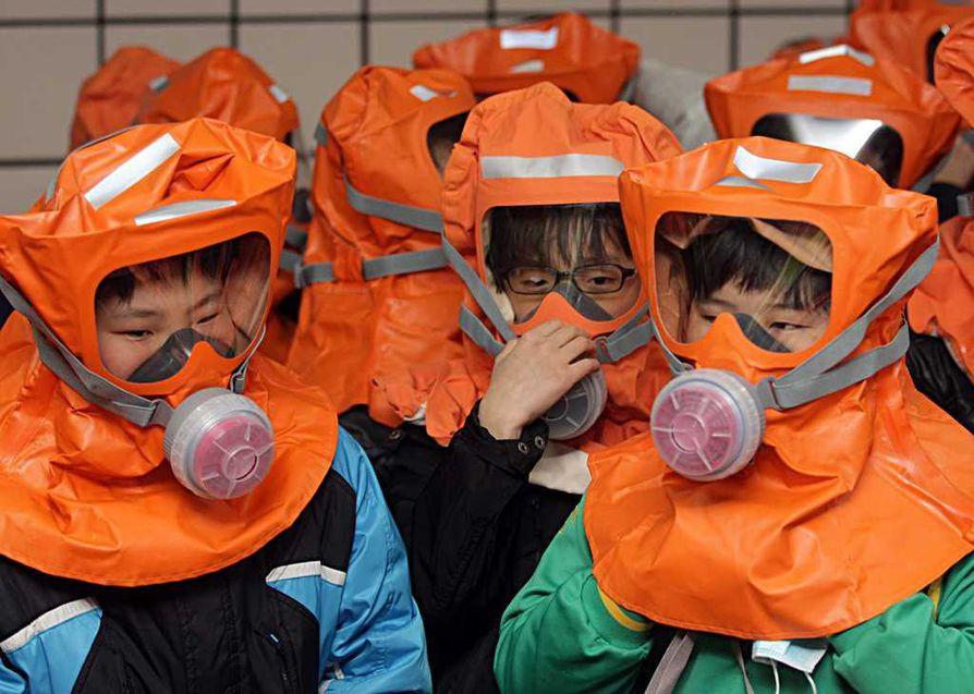 Seoulissa lapset pitävät suojamaskeja ydinsäteilyn pelossa.