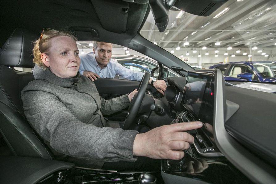 Juhan Auton automyyjä Veli Lämsä esittelee oululaiselle Anna-Kreetta Kilvelle hybridiautoa.