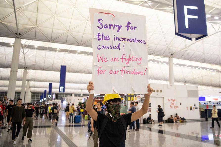"""Ensin he tulivat hakemaan toimittajat. Emme tiedä, mitä sen jälkeen tapahtui"""", ironisoi kirjoittaja. Hongkongissa mielenosoittaja piteli lentokentällä kylttiä: """"Valitamme aiheuttamaamme epämukavuutta. Taistelemme vapaudestamme."""