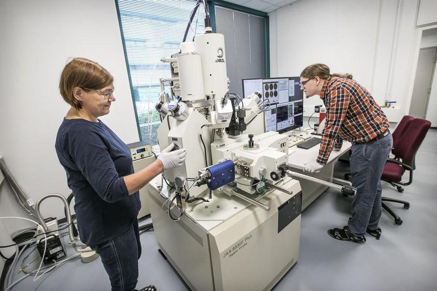 Käyttöinsinööri Leena Palmu  ja geologi Marko Moilanen ja asettavat mikroanalysaattoriin näytettä.