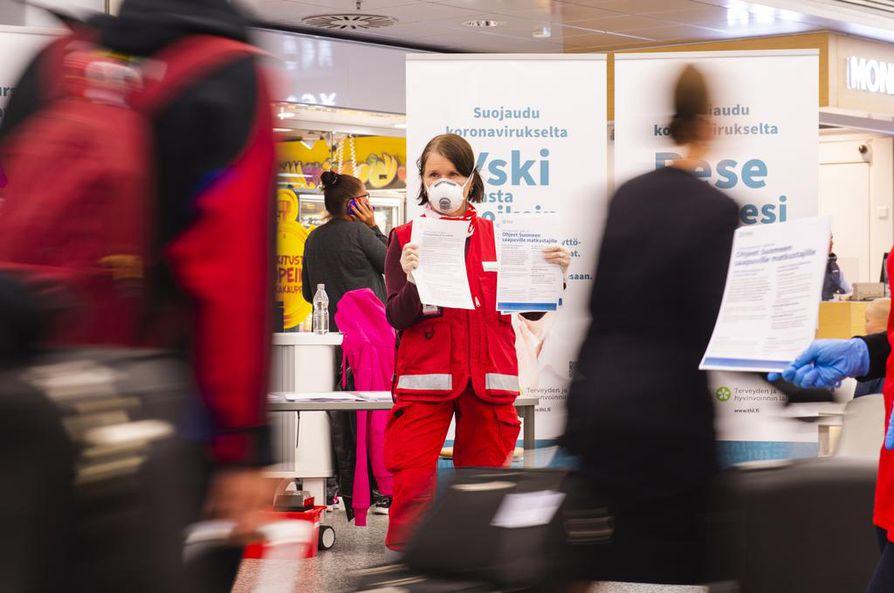 Suomen punaisen ristin (SPR) vapaaehtoistyöntekijät kertovat Helsinki-Vantaan-lentokentällä tietoa koronaepidemiasta ja karanteenikäytännöistä.