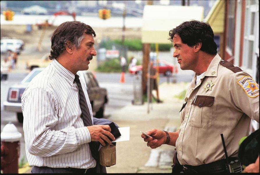 Sylvester Stallone (oik.) on Cop Land -jännityselokuvassa Freddy Heflin, joka alkaa selvittää rikosta. Osallisena on poliisi. Robert De Niro on sisäisen tutkinnan etsivä Moe Tilden, joka selvittää samaa rikosta.