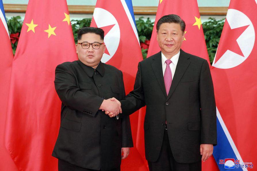 Pohjois-Korean uutistoimiston välittämässä kuvassa maan johtaja Kim Jong-un (vas.) ja Kiinan presidentti Xi Jinping tervehtivät toisiaan tavatessaan Kiinan Dalianissa toukokuussa 2018.