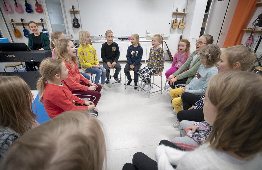 Ritaharjun lapsikuoro harjoittelee laulua piirissä. Ouluhallissa lapset laittavat esiintymisasukseen mustan alaosan ja valkoisen yläosan. Sekä korvatulpat.