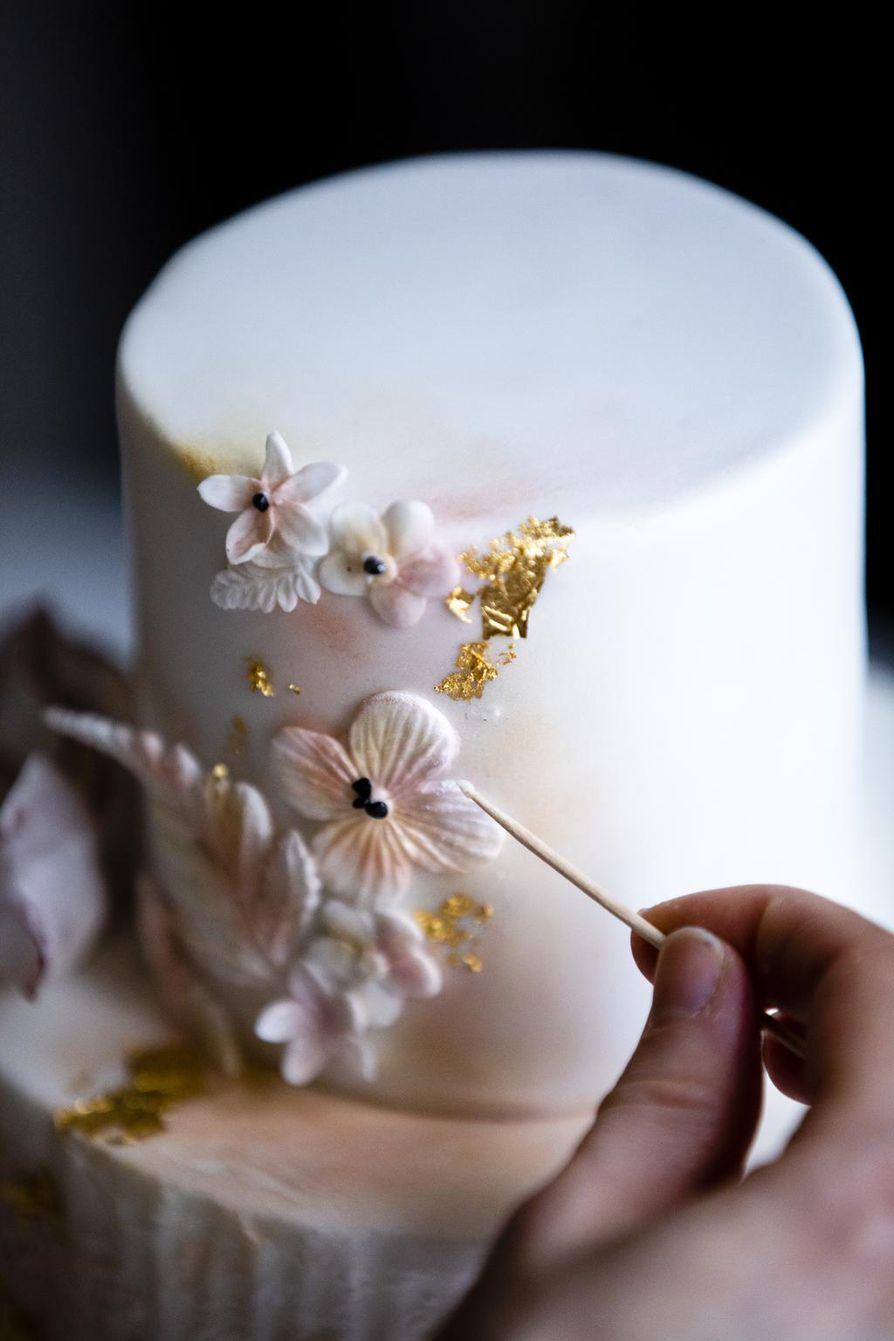 Viimeisen silauksen Lontoon pitsi -nimiselle kakulle antaa 24 karaatin kulta, jota Emma Ivane nostaa kakkuun kuivalla siveltimellä ohuesta kultalehdestä.