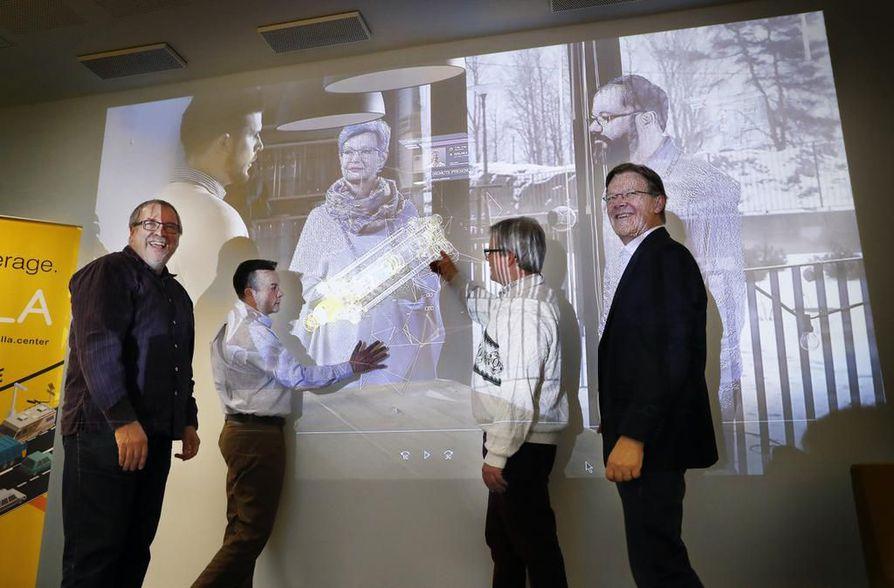 """Hillan johtaja Jaakko Sauvola (toinen vas.) näyttää, miten videolla hologrammin alla oleva """"dataryhelikkö"""" muuttaa aineettomat signaalit näkyviksi viivoiksi. Hillan piirissä toimivat myös Jari-Pekka Rontu Oamkista (vas.), Jukka Riekki sekä Harri Kopola."""