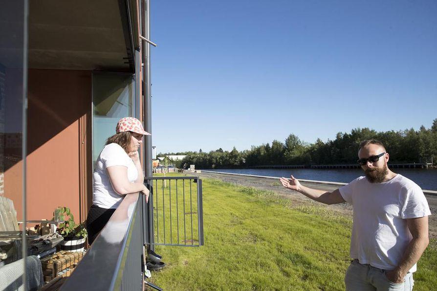 Reeta ja Antti Alakopsa odottelivat vieraita terassillaan Toppilansalmen rannassa.   – Täällä on tosi hauskaa se, miten saattaa olla vierekkäin teollisuusrakennusta ja huvilaa, Reeta Alakopsa kuvailee Toppilansalmen asuinaluetta.