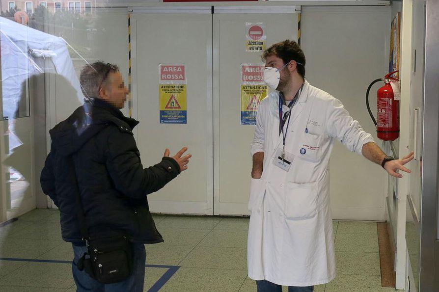Vierailija ja terveydenhuollon työntekijä sairaalan sisäänkäynnillä Padovassa Pohjois-Italiassa.