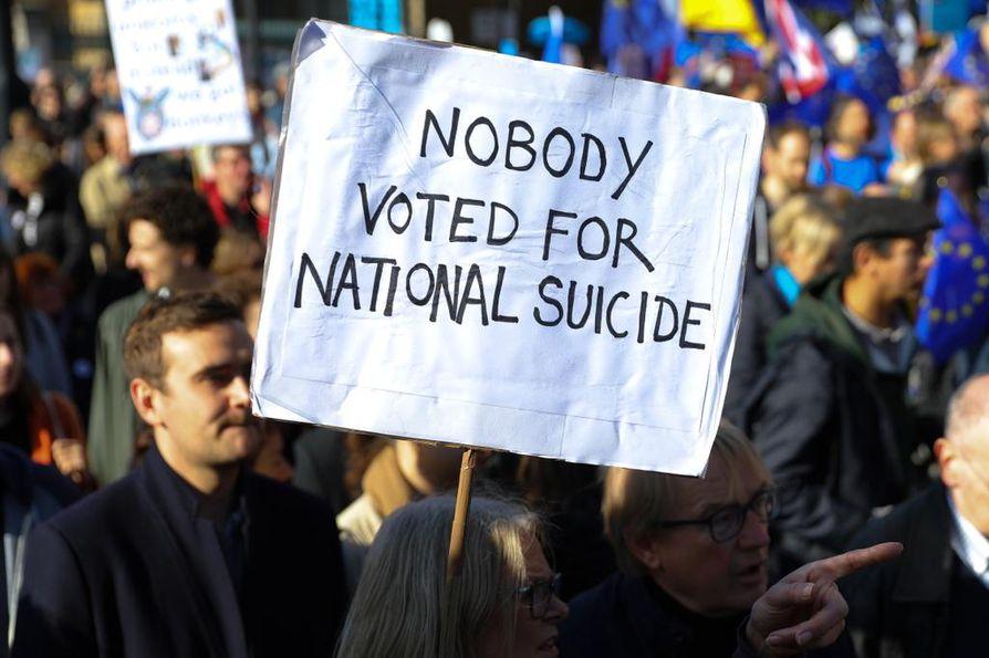 """Mielenosoittajan kyltissä lukee: """"Kukaan ei äänestänyt kansallisen itsemurhan puolesta"""" brittien protestoidessa brexit-asiassa lauantaina Lontoossa. Mielenosoittajat vaativat uutta kansanäänestystä Britannian EU-erosta."""
