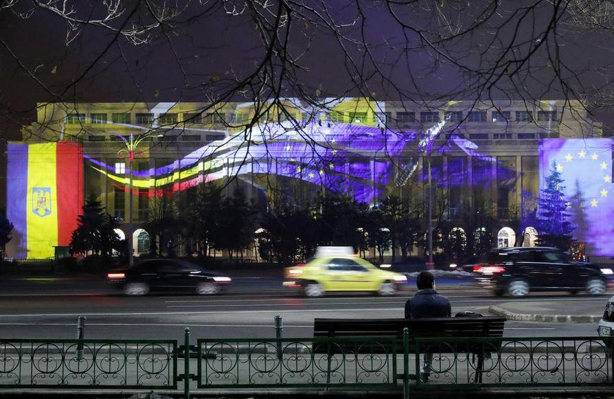 Penkillä istuja ihmettelee Bukarestin hallituspalatsia, joka on poikkeuksellisesti valaistu Euroopan unionin väreillä ja tunnuksilla.