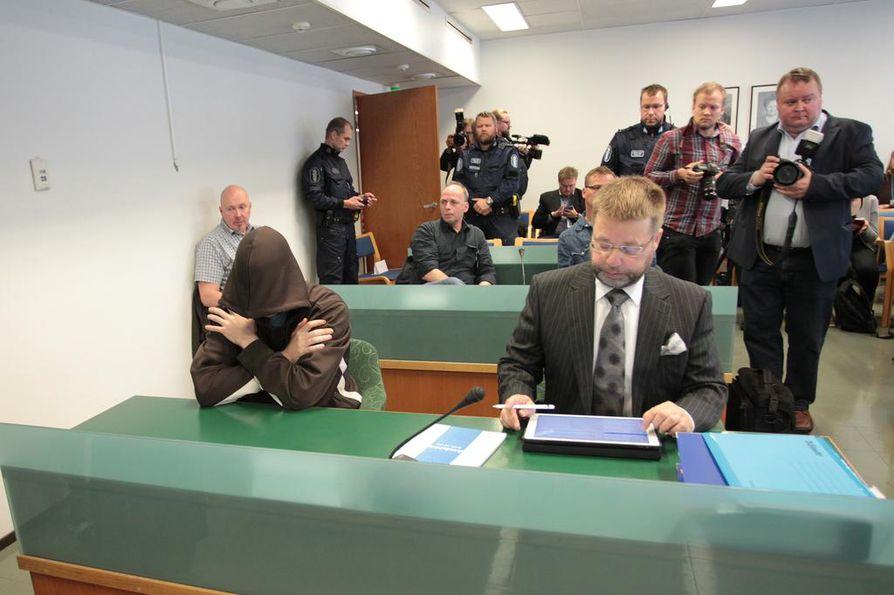 Oikeudenkäynti alkoi Etelä-Karjalan käräjäoikeudessa tiistaiaamuna. Syytetty peitti kasvonsa hupulla.
