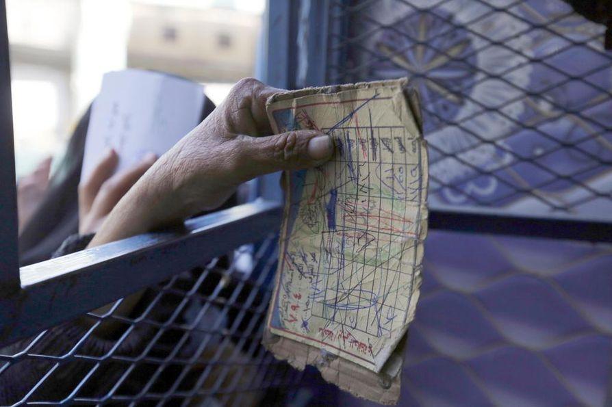 Jemenin sotaa paennut nainen esittää hyväntekeväisyysjärjestölle korttiaan, joka oikeuttaa hänet saamaan ilmaista leipää.