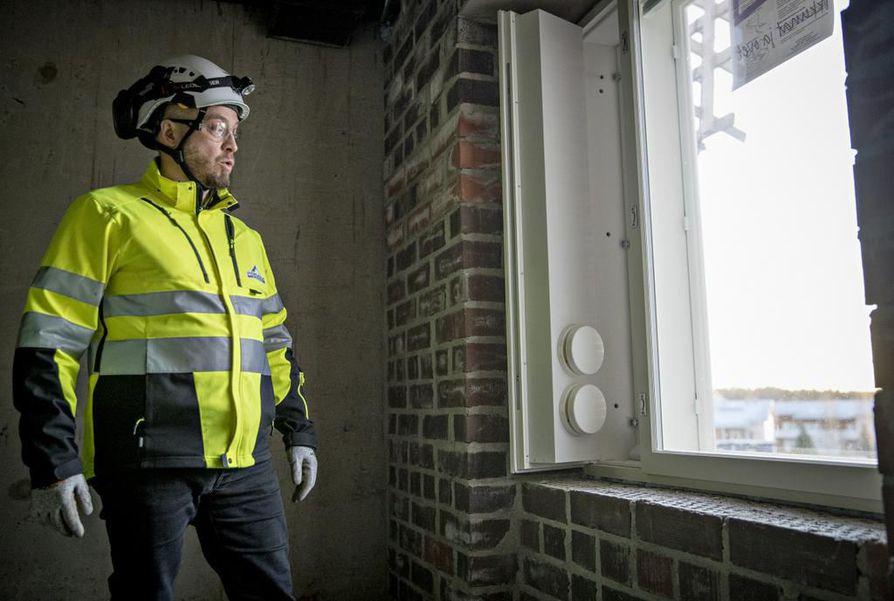 Kaakkurin testitalojen ulkoseinässä on 88 sentin paksuinen tiilimuuraus ja ikkunoissa ilmaa kierrättävät tuloventtiilit.  Ikkunan vieresssä Pohjola Rakennus Oy Suomen työmaapäällikkö Jyrki Kivelä.