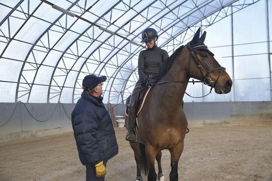 Håkan Wahlman antaa ohjeita Eduardilla ratsastavalle Sara Vainikkalalle. Joskus ratsastajan asentoa pitää korjata myös fyysisesti esimerkiksi siirtämällä jalkaa. Suomessa tähän suhtaudutaan yleensä luontevasti.