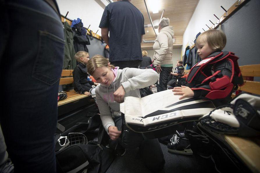 Mervi Haverinen pukemassa maalivahdin varusteita tyttärelleen Elli Haveriselle ennen maanantaisia harjoituksia Linnanmaan jäähallissa. Ellin suosikkipelaajia ovat Lasse Kukkonen ja Patrik Laine.
