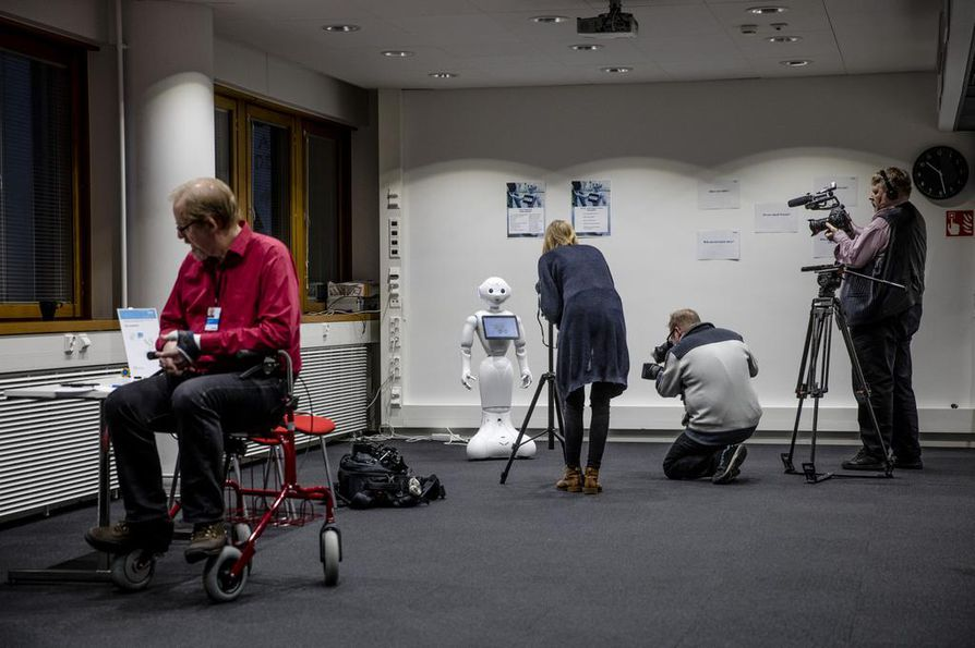 Palvelurobotti Pepper ja älyrollaattori ovat esimerkkejä vanhustenhoitoon ja ikäihmisten arkeen suunnitellusta uudesta teknologiasta. Edessä älyrollaattorin kanssa työskennellyt VTT:n erikoistutkija Olli Kuusisto.