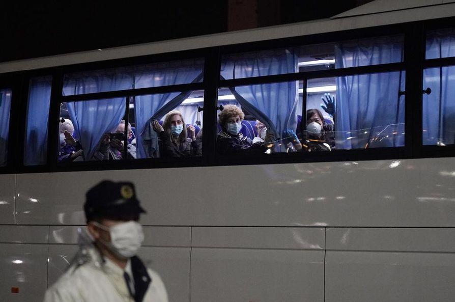 Yhdysvaltain kansalaiset heiluttivat bussin ikkunasta, kun heitä kuljetettiin pois Jokohaman satamasta.