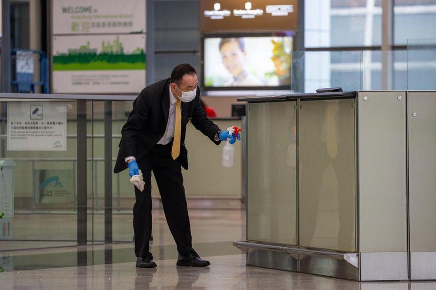 Mies puhdistaa lasivitriiniä Hongkongin kansainvälisellä lentoasemalla. Lentoasemaa ei saa enää käyttää koneen vaihtoon, eivätkä turistit pääse maahan kahteen viikkoon.