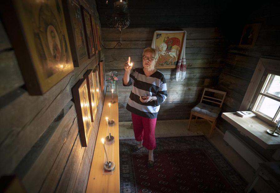 Eeva Tervaskannon sytyttämät mehiläisvahakynttilät valaisevat kotitsasounan ikoniseinää.