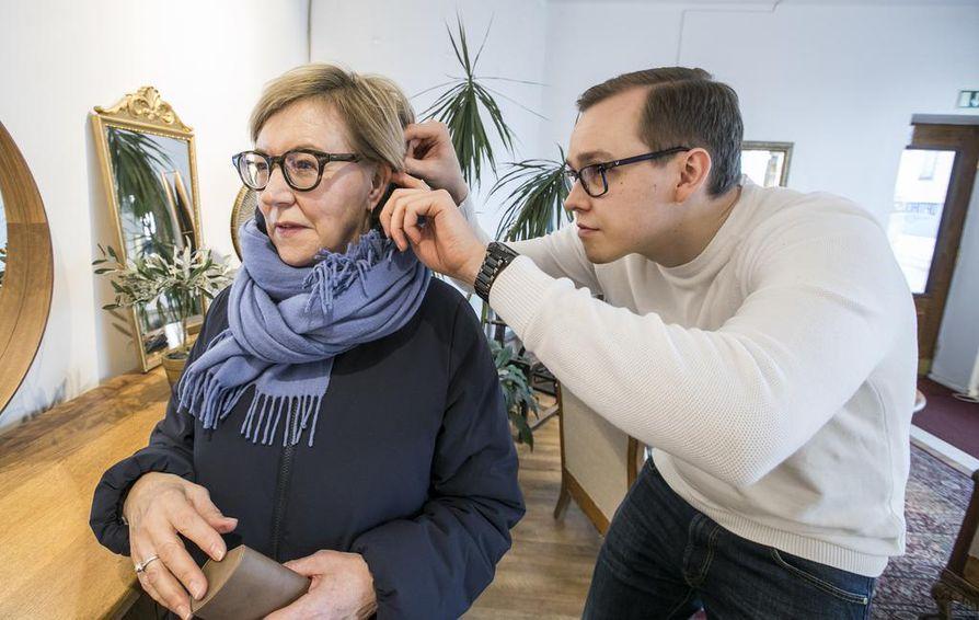 Oululaisliikkeessä harjoitteleva optometristiopiskelija Mikko Jokikokko säätää Arja Hellgrenin äskettäin hankkimia silmälaseja sopivammiksi.