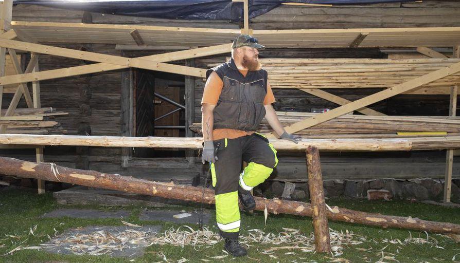 Osuuskunta Artesaaren puuseppä Markku Mulari kuorii pappilan katolle tulevat malkapuut.