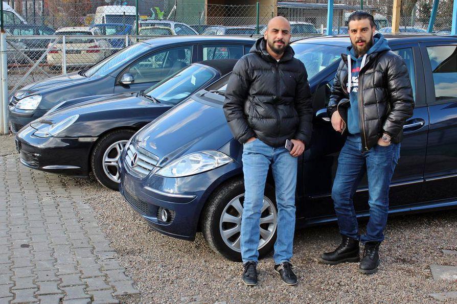 Käytettyjen autojen kauppiaat Kaiser Azam (oik.) ja Ibrahim Azam nojaavat hiljaiseksi muuttuneen kauppansa pihalla pieneen diesel-Mersuun, joka uusimpia päästönormeja täyttämättömänä voi joutua pian ajokieltoon.