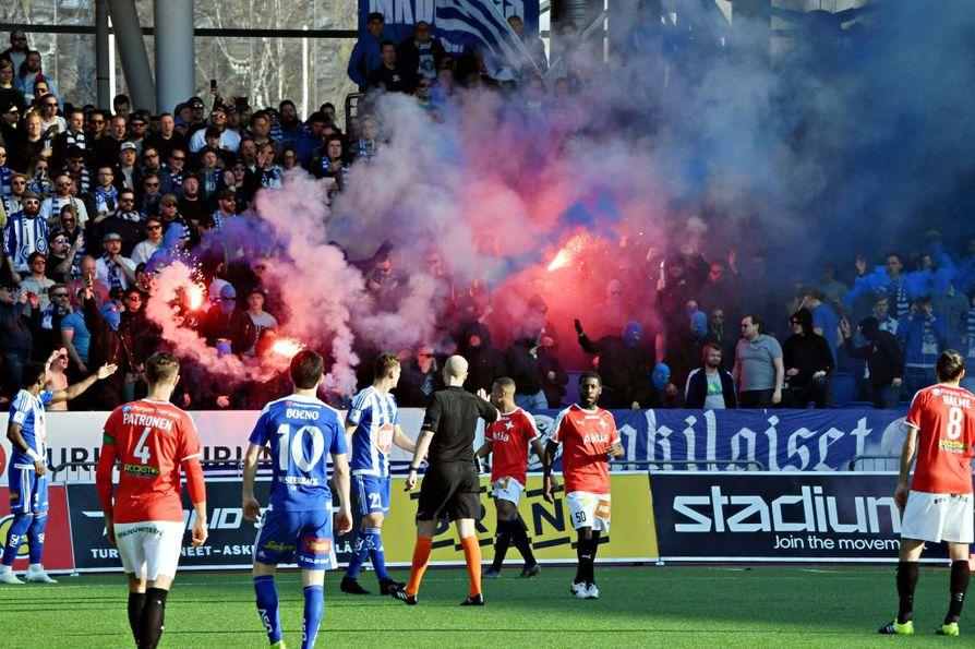 Soihdut palavat HJK:n kannattajien katsomossa jalkapallon Veikkausliigan ottelussa HJK - HIFK Helsingissä 23. huhtikuuta. Poliisi pyysi ennakkoon, ettei otteluun tuotaisi soihtuja tai paukkupommeja.