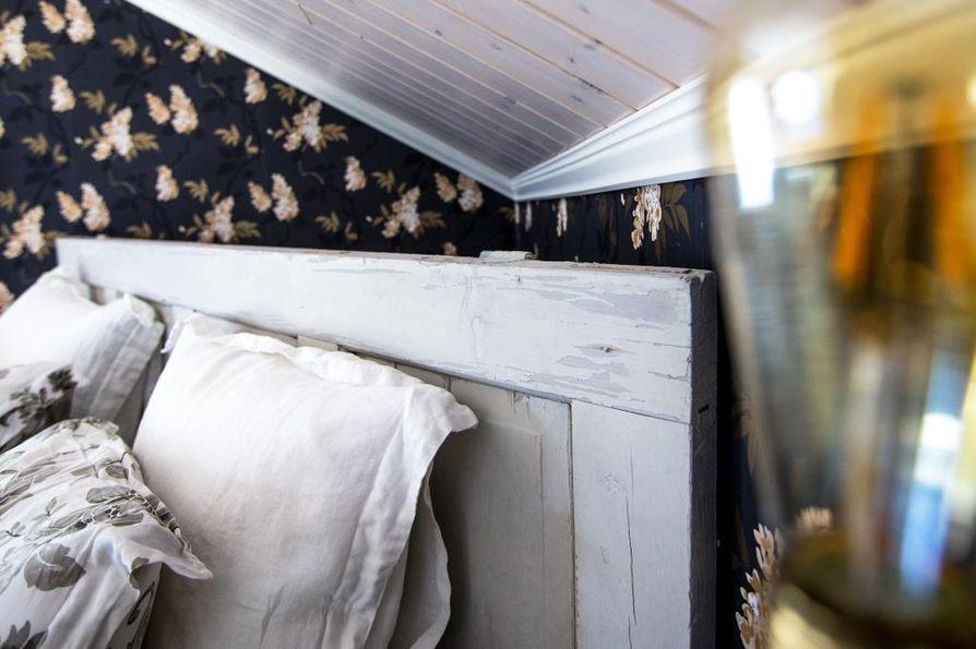 Sängynpääty on vanha ovi. Sisustuksessa on rohkeitakin valintoja, kuten makuuhuoneen musta tapetti, Kaikkialla vallitsee kuitenkin tasapaino.