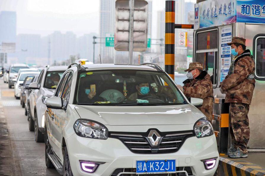 Wuhanissa Kiinassa sotilaat vartioivat liikennettä kaupunkiin ja ulos kaupungista.