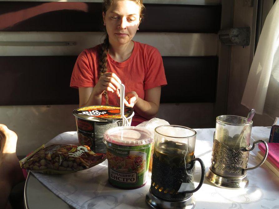 Jokaisessa vaunussa on tarjolla teetä ja kuumaa vettä, jota voi hyödyntää omien eväiden kuten vaikkapa nuudelikeiton tekoon. Anna-Sofia Sysser nauttii välipalaksi myös pähkinöitä.