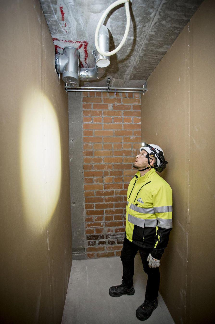 Painovoimaisen ilmanvaihdon poistokanavien määrä nousee talossa kerros kerrokselta. Ensimmäisen kerroksen huoneessa on yksi venttiili katossa. Toisessa kerroksessa on hormi ja katossa yksi venttiili. Kuvassa urakoitsijana toimivan Pohjola Rakennus Oy Suomen työmaapäällikkö Jyrki Kivelä.