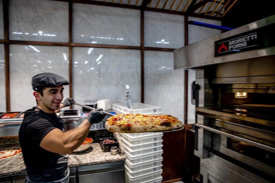 Ruokakaupan kassojen läheisyydessä on pieni pizzeria, jossa Ugur Deniz paistaa pizzaa.