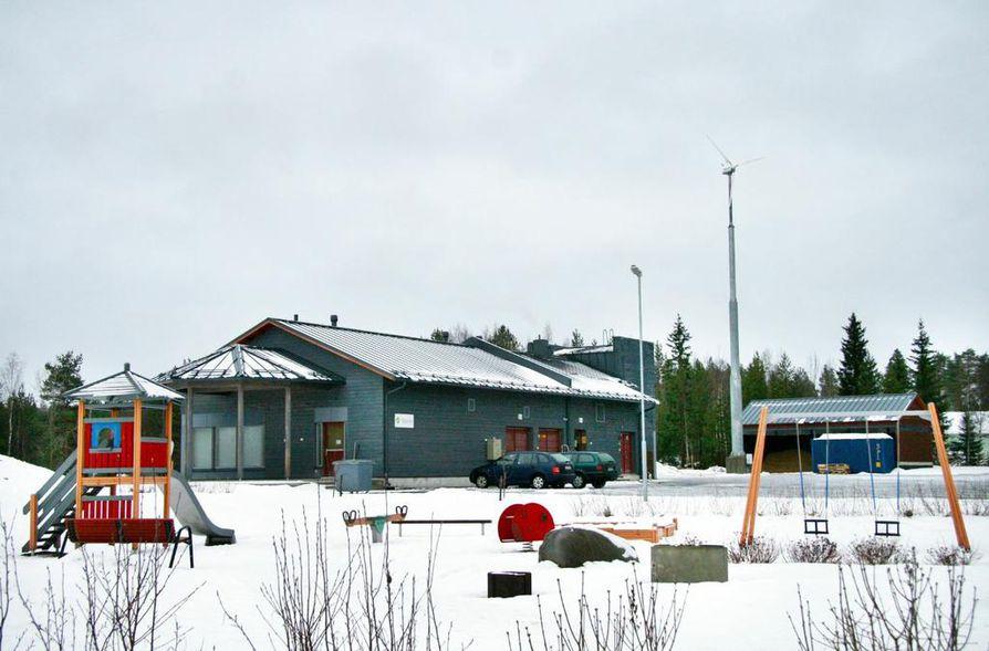Asuinalueen voimalassa tuotetaan sähköä tuulella ja puuhakkeella.